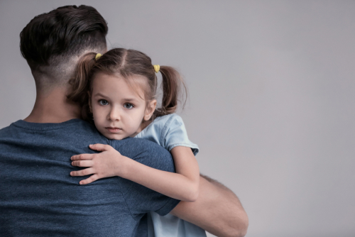 Sad little girl hugging her father on grey background